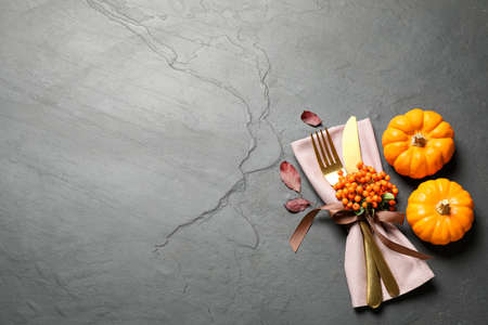 Cutlery, rowan berries and pumpkins on gray table, flat lay with space for text. Thanksgiving day