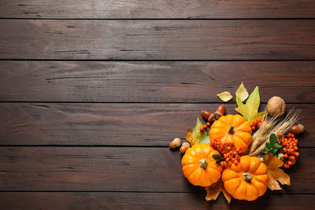 Flat lay composition with vegetables, berries and autumn leaves on wooden table, space for text. Thanksgiving day