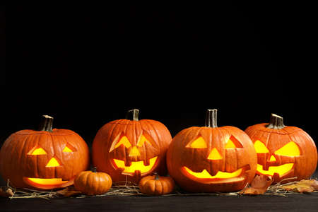 Pumpkin jack o'lanterns on table in darkness, space for text. Halloween decor