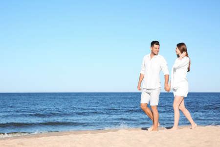 Lovely couple walking on beach. Space for text 写真素材