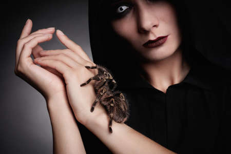 Mysterious witch with spooky spider on dark background, closeup