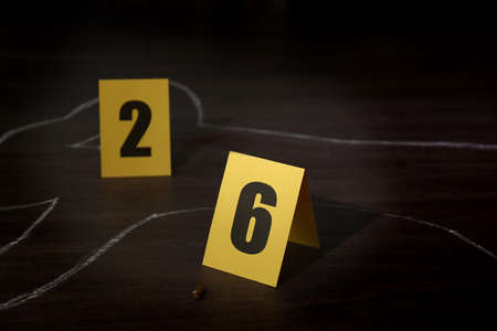Crime scene with chalk outline of human body, bullet shell and evidence markers on wooden floor. Detective investigation