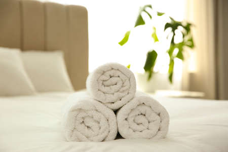 Clean white towels on bed at home