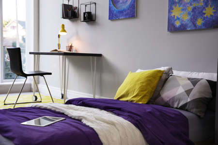 Modern teenager's room interior with comfortable bed, workplace and stylish design elements