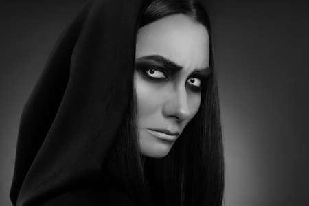 Mysterious witch with spooky eyes on dark background, closeup. Black and white effect