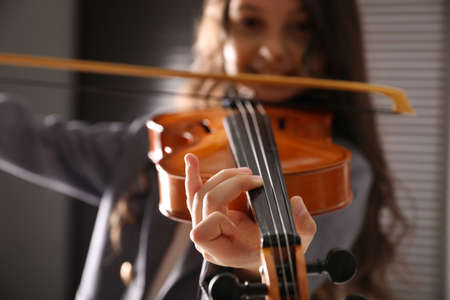 Preteen girl playing violin at music lesson, closeup