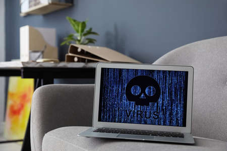 Laptop with virus illustration on gray sofa indoors 版權商用圖片