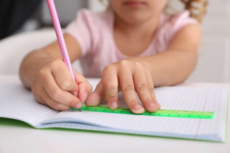 Little girl drawing with ruler and pencil at table, closeup. Doing homework Foto de archivo