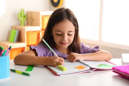 Little girl doing homework at table indoors