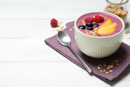 Delicious acai smoothie with fruits served on white wooden table. Space for text
