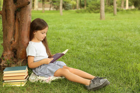 Cute little girl reading book on green grass near tree in park 免版税图像