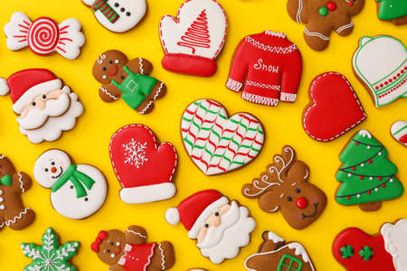 Different Christmas gingerbread cookies on yellow background, flat lay 免版税图像