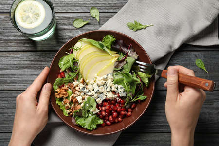 Woman with tasty pear salad at black wooden table, top view