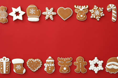 Different Christmas gingerbread cookies on red background, flat lay. Space for text
