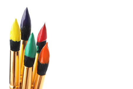 Brushes with colorful paints on white background