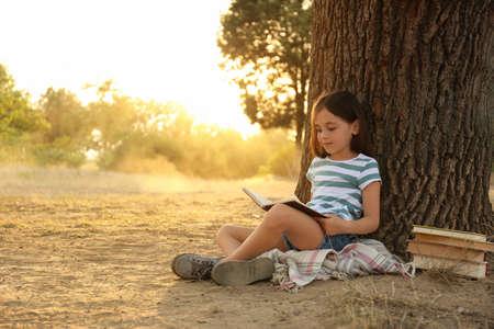 Cute little girl reading book near tree in park