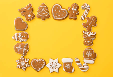 Frame made with different Christmas gingerbread cookies on yellow background, flat lay. Space for text 免版税图像