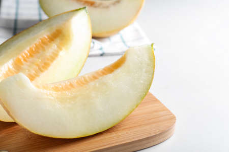 Pieces of delicious honeydew melon on white table
