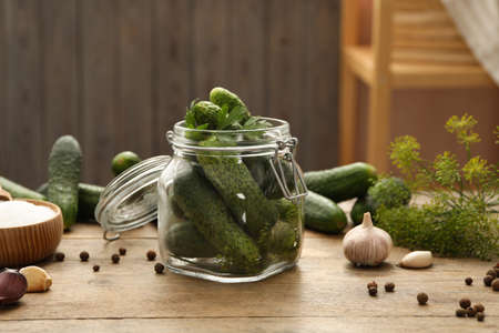 Pickling jar with fresh cucumbers on wooden kitchen table