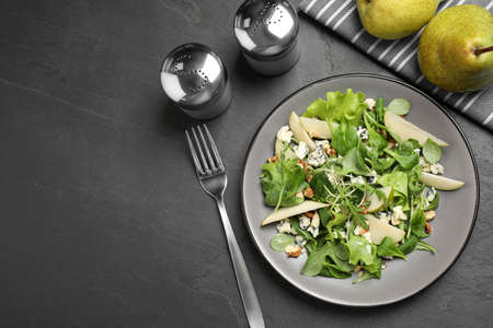 Tasty salad with pear slices served on black table, flat lay. Space for text 免版税图像