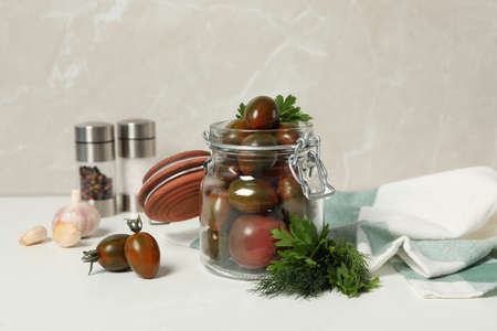 Pickling jar with fresh tomatoes on white table 免版税图像