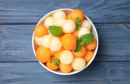 Melon balls and mint in bowl on blue wooden table, top view