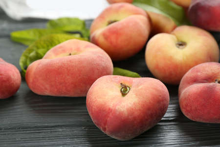 Fresh ripe donut peaches on gray wooden table, closeup Stockfoto
