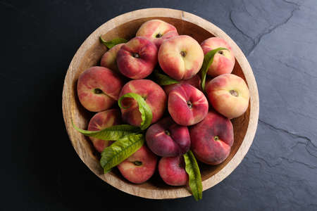 Fresh ripe donut peaches with leaves in bowl on dark table, top view
