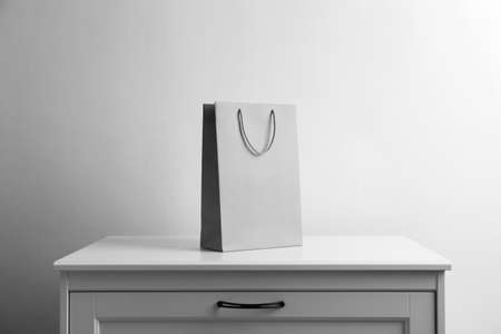 Paper shopping bag on white chest of drawers against light background