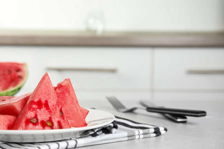 Yummy cut watermelon on table in kitchen, closeup. Space for text