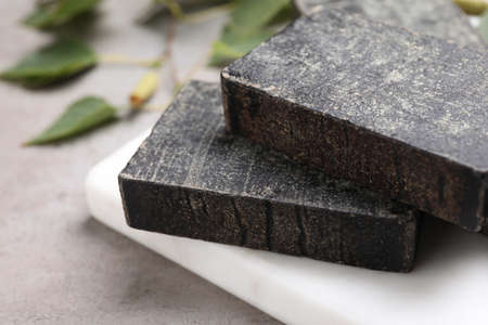 Natural tar soap on light gray stone table closeup