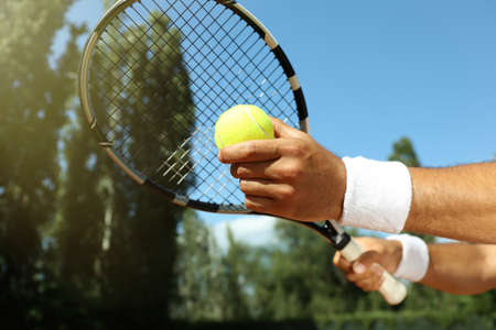 Sportsman preparing to serve tennis ball at court, closeup