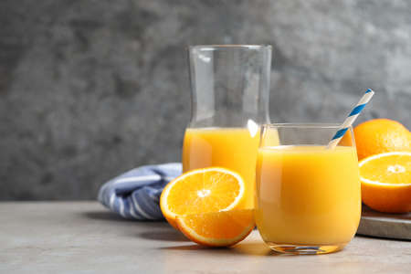 Glass of orange juice and fresh fruits on gray table. Space for text