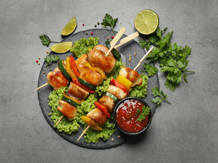Delicious chicken shish kebabs with vegetables on gray table, flat lay