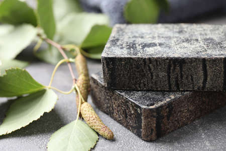 Natural tar soap and birch branch on gray stone table closeup