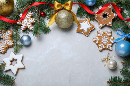 Decorated Christmas cookies, fir tree branches and festive decor on light marble table, flat lay. Space for text