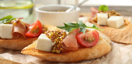 Delicious bruschettas with prosciutto and cheese served on board, closeup. Banner design