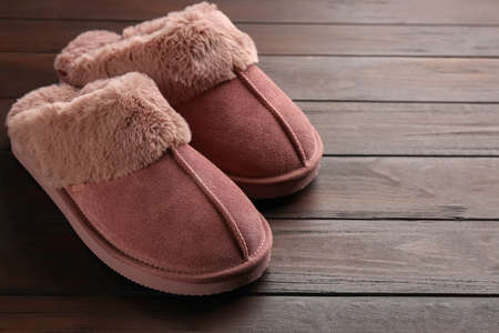 Pair of stylish soft slippers on wooden background. Space for text