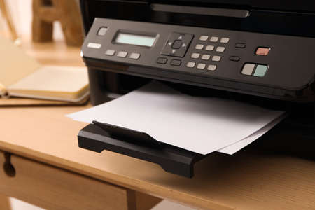 Closeup view of new modern printer with control panel on wooden table