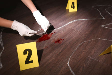 Detective taking blood sample from crime scene, closeup