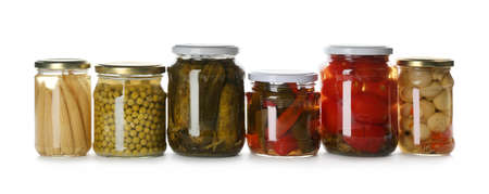 Glass jars with different pickled vegetables and mushrooms on white background