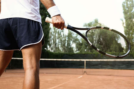 Sportsman playing tennis at court on sunny day, closeup Banque d'images
