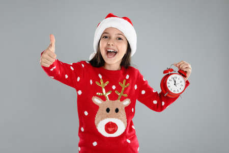 Girl in Santa hat with alarm clock on gray background. New year countdown