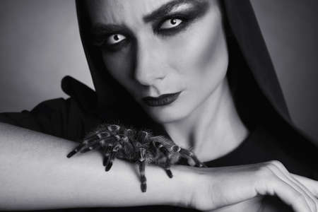 Mysterious witch with spooky spider on dark background, closeup. Black and white effect
