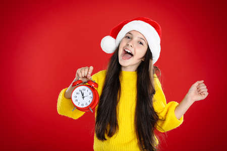 Girl in Santa hat with alarm clock on red background. New year countdown