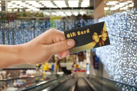 Man holding gift card in shopping mall, closeup Stock fotó