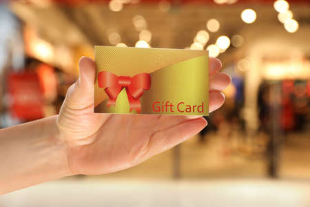 Woman holding gift card in shopping mall, closeup Stock fotó