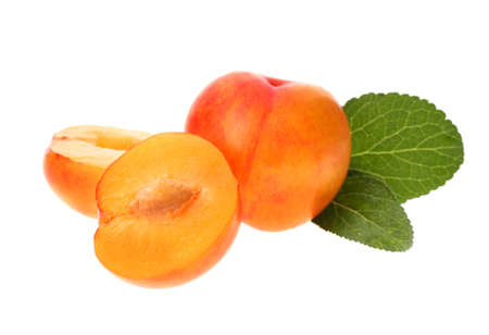 Whole and cut ripe plums with green leaves isolated on white, top view
