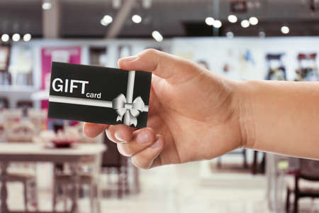 Man holding gift card in cafe, closeup