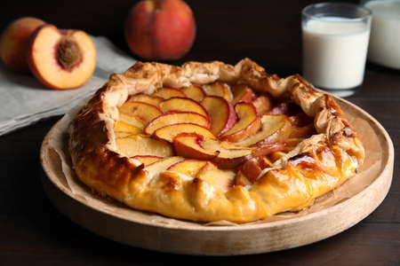 Delicious peach pie and fresh fruits on wooden table, closeup